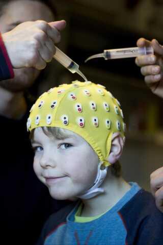 Lidt kold gelé i hullerne på hætten sikrer, at elektroderne senere bedre kan måle, hvordan hjerneaktiviteten er hos eleven.
