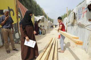UNHCR uddeler planker og værktøj til at sikre flygtningenes telte og barakker i Bar Elias i Bekaa-dalen, Libanon.
