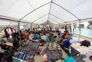 Migranter fra den store migrantkaravane fra Honduras hviler sig i ét af de mange telte, der er sat op i Tijuana. Byen forbereder sig på at tage imod endnu flere end de op mod 2000, som allerede er ankommet.   EPA/JOEBETH TERRIQUEZ