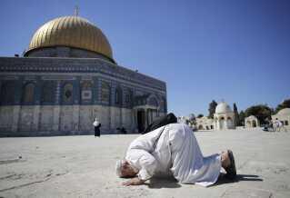 En palæstinenser beder ved Klippemoskeen i Jerusalem.