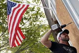 Chris Hooper sætter plader for vinduerne, før orkanen Florence ankommer til Oak Island i North Carolina.