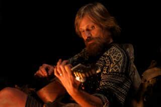 Ude i skoven spiller Ben musik om lejrbålet med sine børn om aftenen.