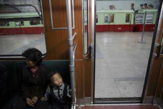 En dreng og en kvinde sidder i et tog under et stop på en station i Pyonyang, hvor en gruppe udenlandske journalister deltog i en statsarrangeret rundvisning.