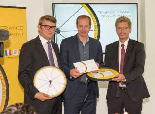 Tidligere erhvervsminister Troels Lund Poulsen og Københavns overborgmester Frank Jensen overbringer i  2016 Danmarks bud på Tour de France til løbsdirektør Christian Prudhomme.