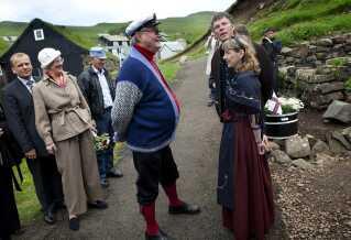 Regentparret på Færøerne i 2010: Prinsen får sig en snak med nogle lokale. mens Dronning Margrethe venter.