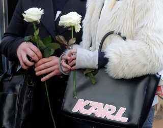Folk stimler sammen foran Chanels butik i Paris for at lægge blomster efter nyheden om Karl Lagerfelds død. Her ses en kvinde med en af de mange tasker med hans navn på.