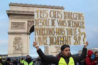 """""""Kære samfundstop, beklager forstyrrelsen, men kan vi ikke alle få lov at leve et værdigt liv', står der på skiltet.    Uligheden i det franske samfund er en af katalysatorerne for den store utilfredshed i protestbevægelsen."""
