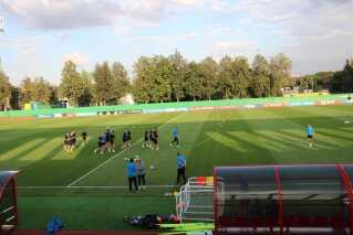 Iva Olivari med Zlatko Dalic på sidelinjen, mens de kroatiske spillere varmer op to dage inden finalen.