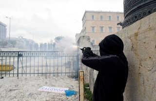 En demonstrant affyrer en røggranat mod politiet.