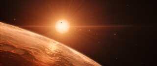 Denne kunstnergengivelse giver et indtryk af udsigten fra en af planeterne i Trappist-1-systemet. Der er minimum syv planeter i kredsløb om stjernen, der ligger 40 lysår fra Jorden, og der kan findes flydende vand på et stort antal af dem.