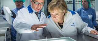 FRANKFURT AM MAIN, GERMANY - MAY 28:  German Chancellor Angela Merkel (R) wears a lab coat as she visits the new production facility for sterile glass vials at the Sanofi pharmaceuticals plant on May 28, 2015 in Frankfurt, Germany. Merkel is visiting the factory, which produces antibiotics and insulin, ahead of the upcoming G7 summit, where the global struggle against antibiotic-resistant bacteria is among topics to be discussed by G7 leaders.  (Photo by Thomas Lohnes/Getty Images)