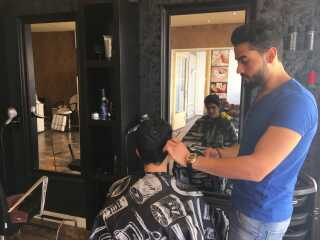 Ahmed Mahmoud Al Rifai har ikke taget den fireårige frisøruddannelse i Danmark, men ifølge ham er det ikke noget, hans kunder går op i.