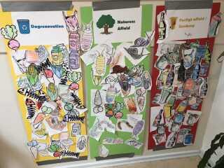 """Børnehavebørnene har farvelagt tegninger og inddelt dem, så de passer til de tre plancher med """"Dagrenovation"""", """"Naturens affald"""" og """"Farligt affald/Genbrug""""."""