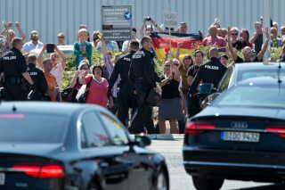 """Demonstranter kalder Tysklands kansler Angela Merkel en """"forræder"""" under hendes besøg på et flygtningecenter i Heidenau tæt på Dresden. De prostesterer mod at byens skal huse nogle af de mange flygtninge der kommer til byen. EPA/JAN WOITAS"""