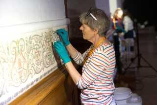 Vandrehallen blev også brugt af repræsentanter fra Nationalmuseet i København, der lige nu er ved at rense vægmalerierne i hele salen. Det er blandt andet nikotinen fra mange års rygning, der har misfarvet malerierne, som altså skal renses med vatpinde. Det er en større opgave.