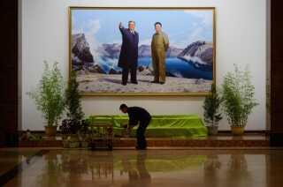 En mand arrangerer blomster under et portræt af Kim Jong-Il (t.h.) i en hotellobby i den nordkoreanske hovedstad, Pyonyang.