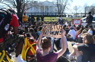 'Beskyt os - ikke våbene', står der på et banner under en demonstration foran Det Hvide Hus med hundredevis af skoleelever, der ønsker en strammere våbenlovgivning i USA. Studerende er gået på gaden i kølvandet på det seneste skoleskyder, hvor 17 personer blev dræbt.