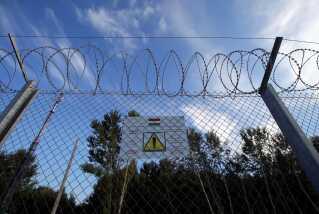 Et skilt advarer om, at det er et lovbrud at ødelægge hegnet i Roszke, Ungarn, ved grænsen til Serbien.