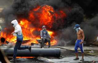 Bål og brand i gaderne i Caracas, Venezuela, under mandagens protester.