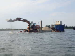 Her er en gravemaskine i gang med at sprede sand ud i Odense Fjord, som en del af projektet på Syddansk Universitet, der ser på, om sand kan få ålegræs til at gro bedre i de danske vandområder.