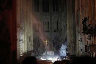 Røg stiger op omkring alteret i Notre Dame. Billeder dagen derpå afslører store skader i katedralen.