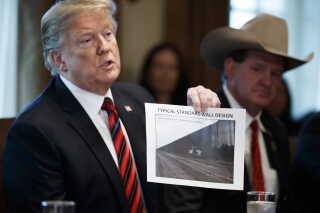 Donald Trump fremviser et billede af en prototype af muren.