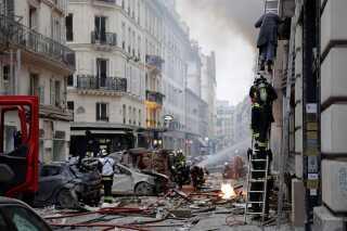 En kvinde hjælpes ud af ejendommen af brandmænd.