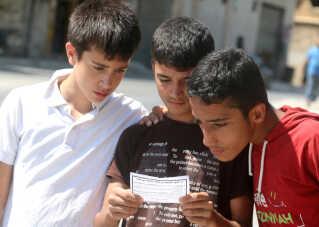 Tre drenge har fået fat i en af de flyers, der ar den syriske hær er blevet kastet ud over byen.