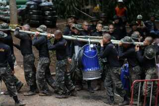 Thailandske soldater bærer en pumpe ved grotten.