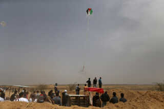Palestinians set a kite on fire to be thrown at the Israeli side during clashes at a protest demanding the right to return to their homeland, at the Israel-Gaza border in the southern Gaza Strip, April 20, 2018. REUTERS/Ibraheem Abu Mustafa