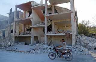 En syrer stopper sin motocykel foran ruinerne af en bygning i Idlib. Allerede inden offensiven for alvor er indledt, er byen meget medtaget af den lange borgerkrig.