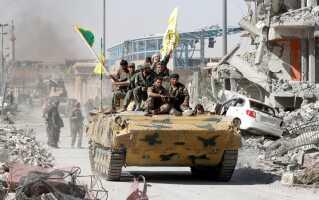 Styrker fra den Frie Syriske Hær ruller ind i Raqqa i en kampvogn.
