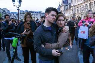 Der bliver givet kram og trøstet foran Notre Dame. Branden har ramt franskmændene hårdt.