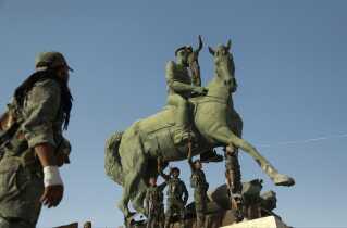 Syriske kurdere poserer på en statue af Basel al-Assad, den syriske præsidents afdøde storebror, i den nordøstlige by Hasakeh i Syrien.