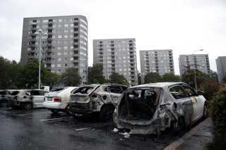 Udbrændte biler på en parkeringsplads i Göteborg. I en tilsyneladende koordineret aktion stak grupper af unge ild til parkerede biler flere steder i Sverige.