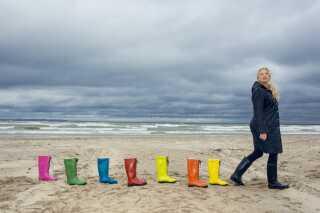 Ilse Jacobsen på Hornbæk strand med de velkendte, farverige gummistøvler.