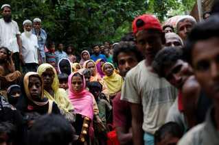 Rohingya-flygtninge venter på at få udleveret mad tæt ved flygtningelejren Kutupalong i Bangladesh.