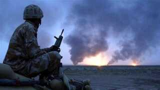 En soldat betrager en række brande udløst af krigshandlinger.