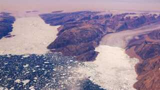 Fenris Gletsjeren i forgrunden og Helheim Gletsjeren i baggrunden, gletsjerne ligger i Sermilik fjorden nær Tasiilaq. Fenris har trukket sig mere end 5.000 meter tilbage siden 1933, hvor dette billede blev taget under anden halvdel af Knud Rasmussens 7. Thuleekspedition. Helheim Gletsjeren er den tredje største i Grønland (efter Jakobshavn Isbræ i Diskobugten og Kangerdlugssuaq Gletscheren på Østkysten).