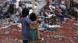 Børn fra Bangladesh kigger på ruinerne på Rana Plaza, hvor 1.131 er døde efter et bygningskollaps.