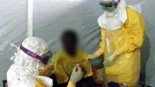 En mand, der er smittet med ebola-virus, bliver hjulpet til at spise af læger.