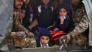 Befriede børn bliver transporteret væk af militæret under det blodige angreb.