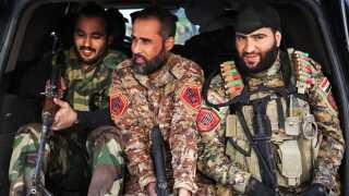 Et medlem af Abu al-Fadl al-Abbas militsen holder vagt syd for Bagdad. Foran vajer et flag med en af shiismens vigtigste religiøse skikkelser, Hussein.