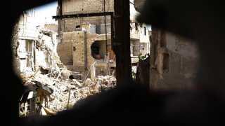 Udsigten fra et af snigskytternes huller i Damaskus-forstaden Qaboun. Gaderne er sønderbombede efter tre års kampe.