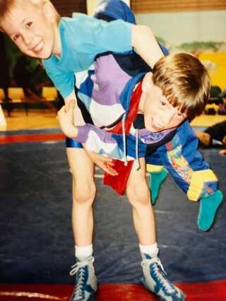 En ung Mark O. Madsen løfter sin yngre fætter Micki over skulderen til et stævne i Lindeskovhallen i Nykøbing F.