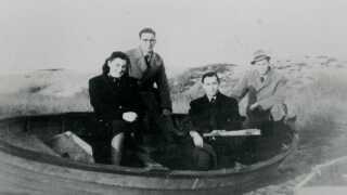"""Her ses fire jødiske søskende fotograferet foran den robåd, som fragtede dem til Sverige. Med i båden var også deres moster og en fisker. Kort før ankomsten til Rå syd for Helsingborg knækkede den ene åre. En af dem holder årestumpen. Bag på det originale foto står: """"Kære Far. Hermed en Hilsen fra os alle fire."""" (Foto: (ukendt fotograf) © Frihedsmuseet/Nationalmuseet)"""