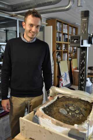 Søren Bagge ved et opgravet udsnit af fundet, som blev analyseret af museumsorganisationen ROMU via CT-scanning.
