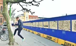 Kristian Djurhuus med kunstnernavnet 'Mormor' i Odense foran sit 20 meter lange kunstværk på hegnet ved byggepladsen på Thomas B. Thriges Gade. Illustrationerne skildrer Odenses historie.