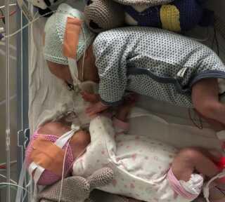 Billede af tvillingerne, da de var halvanden måned gamle. Her er det første gang, de begge er stærke nok til at ligge sammen.