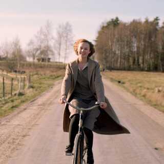 Astrid Lindgren skildres som en energibombe, som bliver forvandlet til en voksen kvinde, da hun bliver gravid. Her er det Alba August i rollen som forfatteren.